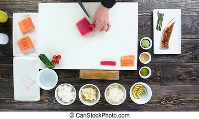 Sushi preparation, wooden table. Hands cutting tuna.