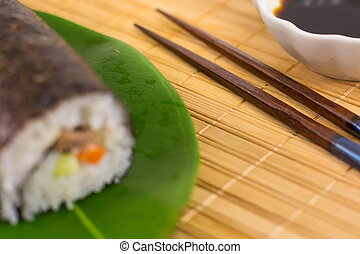 Sushi roll and chopsticks on bamboo tablecloth