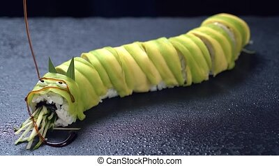 Traditional Japanese dish - Sushi roll pour sauce on a dark...