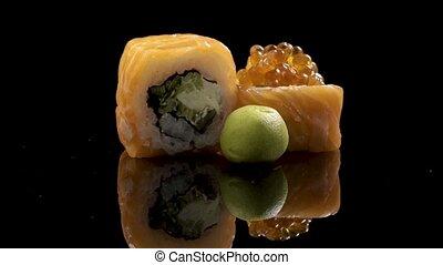 Sushi roll rotated on black background. Sushi japanese food...