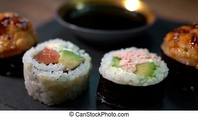 Sushi roll set on the black plate. Japanese food.