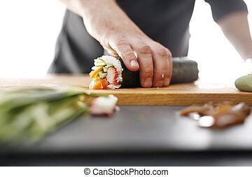 Sushi roll - Sushi master preparing sushi in Japanese...