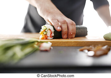 Sushi roll - Sushi master preparing sushi in Japanese...