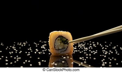 sushi roll with salmon and caviar on black background rotating.