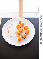 Sushi roll with salmon, philadelphia on a white plate on a black background top view.