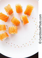 Sushi roll with salmon, philadelphia on a white plate, top view. Close-up. Beautifully decorated plate.