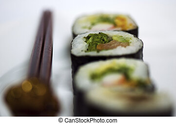 Sushi rolls - A line of sushi rolls on a plate with some ...