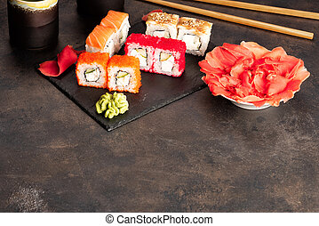 Sushi rolls and sashimi in a black stone plate.