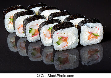 Sushi rolls Futo Maki on a black background.