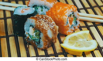 Sushi Rolls on a Bamboo Mat Rotates. Variety of types sushi...