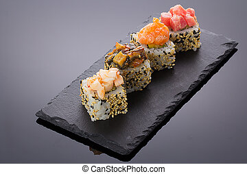 Sushi rolls on a stone plate