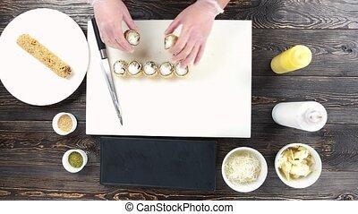 Sushi rolls on cutting board. Hands of chef, unagi maki.