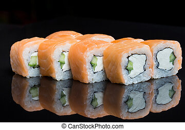 Sushi rolls philadelphia on a black background.