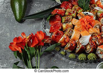 Sushi rolls set on a crystal tray. Rolls: Philadelphia, ...