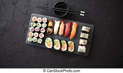 Sushi rolls set with salmon and tuna fish served on black...