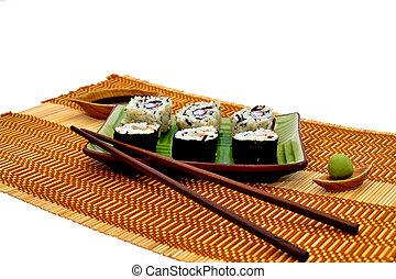 Sushi rolls soya sauce wassabi and wooden chopsticks
