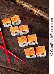 Sushi rolls with chopsticks on a wooden table