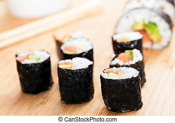 Sushi rolls with salmon, avocado, rice in seaweed and ...