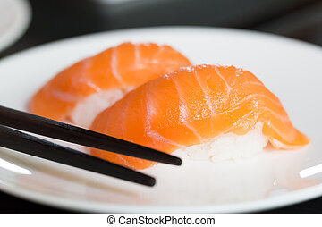 Sushi salmon on white plate with chopstick