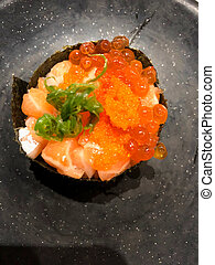 Sushi salmon shrimp eggs on black dish