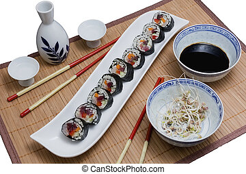 Sushi served with soya sprouts and sake and two pairs of chopsticks on dark background