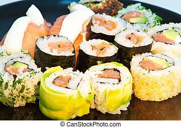 Sushi set in a black plate close up
