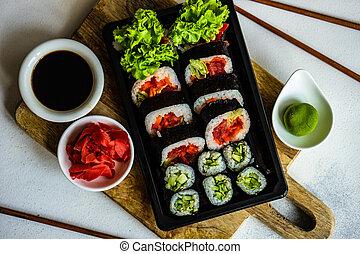 Sushi Set sashimi and sushi rolls served on stone slate - ...
