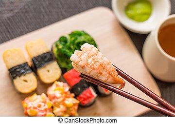Sushi set with chop sticks, wasabi served on wooden slate,...