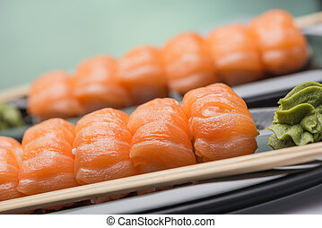 Sushi with a light-salted salmon, wooden sticks and sauce of...