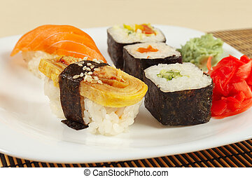 Sushi with omelet with eel and with salmon and rolls on bamboo mat close up.
