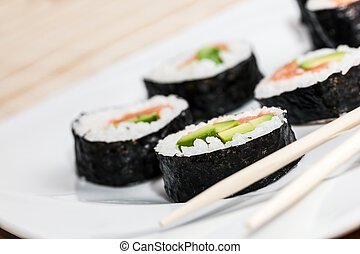 Sushi with salmon, avocado, rice in seaweed and chopsticks ...