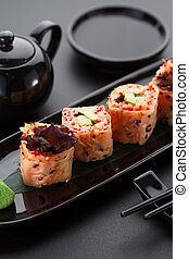 Sushi with shrimp and red tobiko in mamenori on a black plate