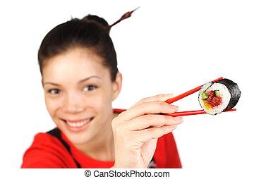 Sushi woman - Beautiful woman holding a tuna maki sushi. ...