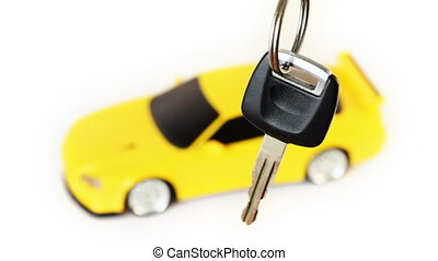 suspended key, back in defocus rotates toy car on white...
