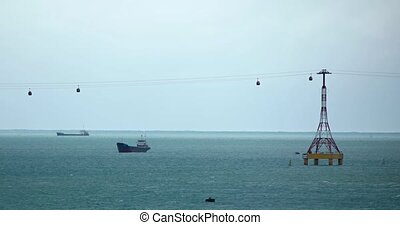 Suspended cable cars carry tourists over a shipping channel near Nha Trang, Vietnam, as commercial vessels lie at anchor, below. Footage 4k