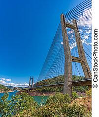 Suspension bridge and dam over blue sky, vertical composition