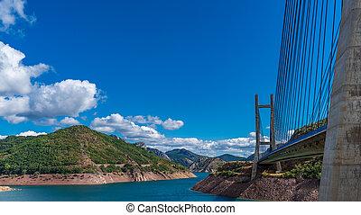 Suspension bridge and dam over blue sky