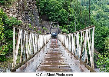 Suspension bridge. Old car on the car bridge