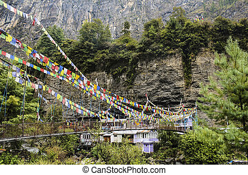 Suspension bridge with prayer flags in the village