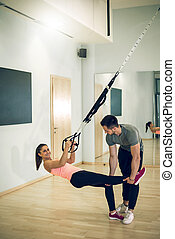 Suspension exercise with personal trainer.