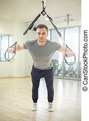 Suspension straps training in modern fitness facility -...