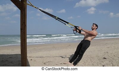 Suspension training with fitness straps on the beach