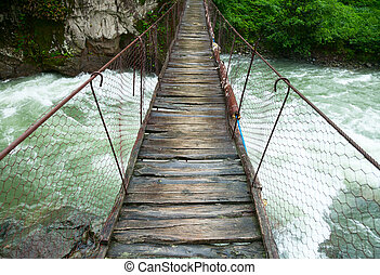 Suspension walking bridge - Rickety foot bridge over white...