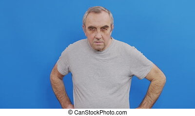Suspicion concept. Serious mature man looking to camera, blue studio background