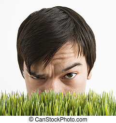 Suspicious man behind grass. - Asian young man looking over...