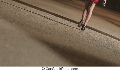 Suspicious man in cloak pursues young woman in short skirt and heels in the park at night
