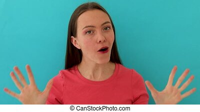 Sceptical woman in bright clothes rising eyebrow and gesturing while talking and standing over blue background