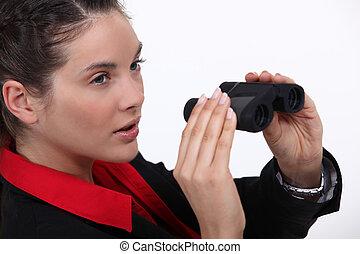 Suspicious woman watching through binoculars