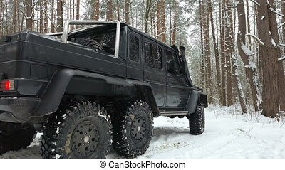 SUV 6x6 driving on a snow-covered road in winter forest. Off-road