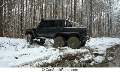 SUV 6x6 overcomes off-road in the winter forest. Jeeping